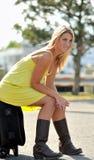 Schöne junge blonde Frau, die auf Koffer sitzt Lizenzfreies Stockbild