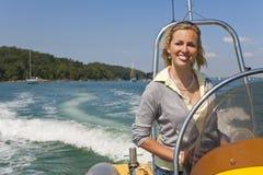 Schöne junge blonde Frau, die ein Schnellboot antreibt Lizenzfreies Stockbild