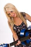 Schöne junge blonde Frau, die eine Gitarre spielt Stockbilder