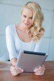 Schöne junge blonde Frau, die eine Tablette hält Lizenzfreie Stockbilder