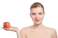 Schöne junge blonde Frau, die einen roten Apfel anhält Lizenzfreie Stockfotos