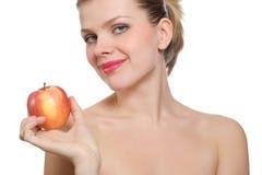 Schöne junge blonde Frau, die einen roten Apfel anhält Stockbild