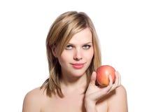 Schöne junge blonde Frau, die einen roten Apfel anhält Lizenzfreies Stockbild