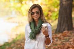 Schöne junge blonde Frau, die einen Tasse Kaffee trinkt Stockfoto