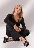 Schöne junge blonde Frau, die in einer schwarzen Ausstattung sitzt Stockfotografie