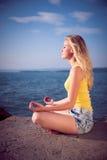 Schöne junge blonde Frau, die herein auf einem Strand bei Sonnenaufgang meditiert Lizenzfreies Stockbild