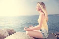 Schöne junge blonde Frau, die herein auf einem Strand bei Sonnenaufgang meditiert Lizenzfreie Stockfotos