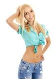 Schöne junge blonde Frau, die ihr Haar lächelt und berührt Stockbild