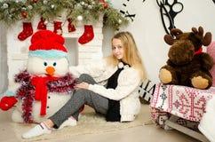 Schöne junge blonde Frau, die im neuen Jahr mit Geschenken nahe dem Kamin und dem Schneemann sitzt Lizenzfreies Stockfoto