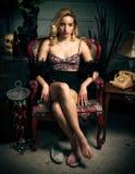 Schöne junge blonde Frau, die im Stuhl sitzt Stockfoto