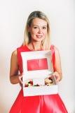 Schöne junge blonde Frau, die Kasten mit 6 kleinen Kuchen hält Lizenzfreie Stockfotos