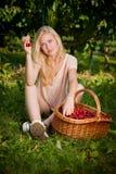 Schöne junge blonde Frau, die Kirschen auf einer heißen Quelle erntet Stockfotos