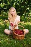 Schöne junge blonde Frau, die Kirschen auf einer heißen Quelle erntet Stockfotografie