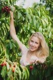 Schöne junge blonde Frau, die Kirschen auf einer heißen Quelle erntet Stockfoto