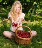 Schöne junge blonde Frau, die Kirschen auf einer heißen Quelle erntet Lizenzfreie Stockfotografie