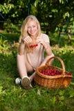 Schöne junge blonde Frau, die Kirschen auf einer heißen Quelle erntet Lizenzfreie Stockbilder