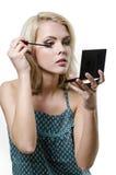 Schöne junge blonde Frau, die Make-up tut stockfotos