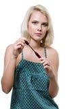 Schöne junge blonde Frau, die Make-up tut stockfoto