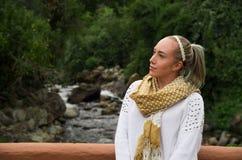 Schöne junge blonde Frau, die mit einem Fluss im Hintergrund aufwirft Lizenzfreie Stockfotos
