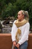 Schöne junge blonde Frau, die mit einem Fluss im Hintergrund aufwirft Lizenzfreies Stockbild