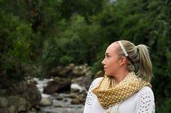 Schöne junge blonde Frau, die mit einem Fluss im Hintergrund aufwirft Stockbild