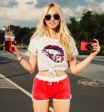 Schöne junge blonde Frau, die mit einem Getränk und einem Sommertag der roten Kamera der Weinlese heißen aufwirft Stockbilder
