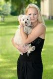 Schöne junge blonde Frau, die mit ihrem Hund aufwirft Lizenzfreies Stockfoto