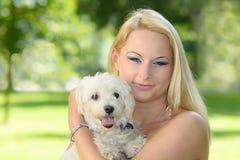 Schöne junge blonde Frau, die mit ihrem Hund aufwirft Stockbild