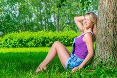 Schöne junge blonde Frau, die nahe dem Baum sitzt Lizenzfreie Stockfotos