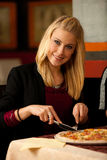 Schöne junge blonde Frau, die Pizza im Restaurant isst Lizenzfreie Stockfotos