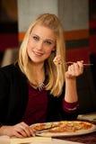Schöne junge blonde Frau, die Pizza im Restaurant isst Stockfotografie