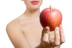 Schöne junge blonde Frau, die roten Apfel anbietet Stockfotografie