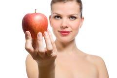 Schöne junge blonde Frau, die roten Apfel anbietet Lizenzfreie Stockbilder