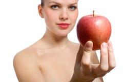 Schöne junge blonde Frau, die roten Apfel anbietet Lizenzfreie Stockfotografie