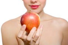Schöne junge blonde Frau, die roten Apfel anbietet Stockbild