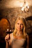 Schöne junge blonde Frau, die Rotwein in einem Weinkeller schmeckt Stockfotografie