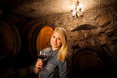 Schöne junge blonde Frau, die Rotwein in einem Weinkeller schmeckt Stockfotos