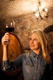 Schöne junge blonde Frau, die Rotwein in einem Weinkeller schmeckt Lizenzfreie Stockbilder