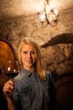 Schöne junge blonde Frau, die Rotwein in einem Weinkeller schmeckt Lizenzfreie Stockfotos