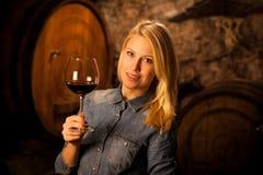 Schöne junge blonde Frau, die Rotwein in einem Weinkeller schmeckt Stockbilder