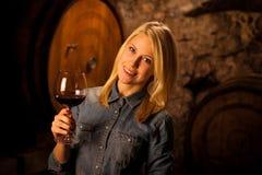 Schöne junge blonde Frau, die Rotwein in einem Weinkeller schmeckt Stockfoto