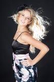 Schöne junge blonde Frau, die schwarzes Kleid trägt Lizenzfreies Stockfoto