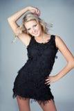 Schöne junge blonde Frau, die schwarzes Kleid trägt Lizenzfreies Stockbild