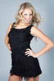 Schöne junge blonde Frau, die schwarzes Kleid trägt Lizenzfreie Stockfotos