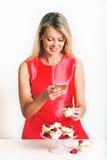 Schöne junge blonde Frau, die am Tisch sitzt Stockfoto