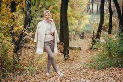Schöne junge blonde Frau, die Zeit im Herbstpark verbringt lizenzfreie stockfotos