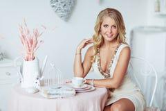 Schöne junge blonde Frau in einem beige Kleid, das auf einem Stuhl sitzt Lizenzfreies Stockbild