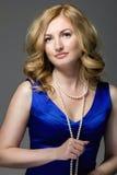 Schöne junge blonde Frau in einem blauen Kleid mit Perle bördelt Lizenzfreies Stockbild