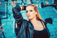 Schöne junge blonde Frau in einem schwarzen Körper in der Lederjacke, die auf dem Hintergrund der gemalten Wand auf der Straße st Lizenzfreie Stockfotografie