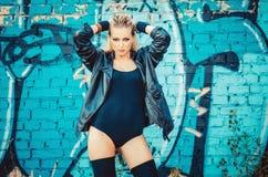 Schöne junge blonde Frau in einem schwarzen Körper in der Lederjacke, die auf dem Hintergrund der gemalten Wand auf der Straße st Lizenzfreies Stockbild